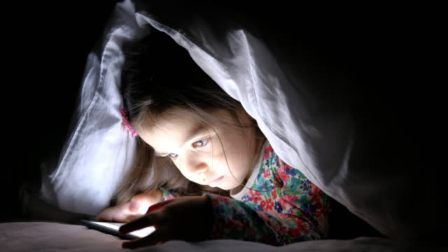 Girls using digital tablet under blanket