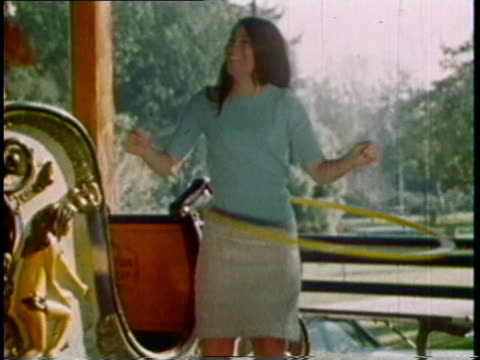 1975 film montage ms pan girls using hula hoop on carousel/ ws surfer using hula hoop/ ws people using hula hoops on fire truck and miniature train/ ws zi girl on lawn with hula hoop/ cu hula hoop logo - advertisement stock videos & royalty-free footage