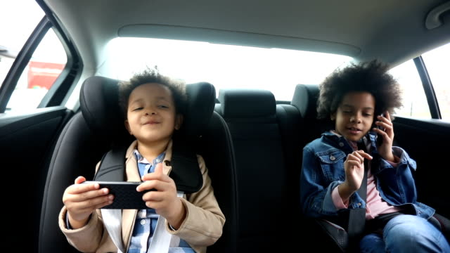 girls using smart phones in back seat of car - sibling stock videos & royalty-free footage