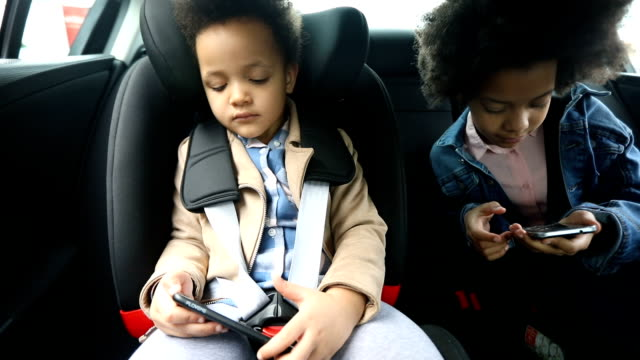 girls using smart phones in back seat of car - vehicle seat stock videos & royalty-free footage