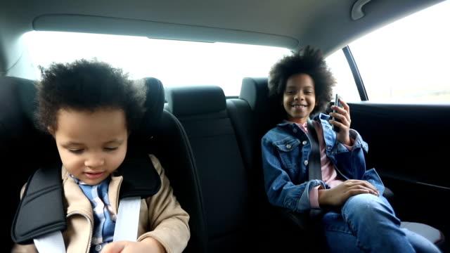 stockvideo's en b-roll-footage met meisjes met behulp van slimme telefoons in de achterbank van de auto - passagiersstoel