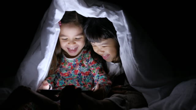 Girls using tablet under blanket
