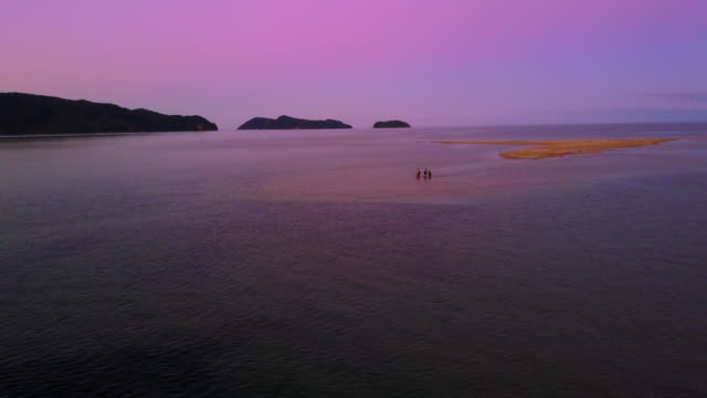 Girls walk in shallow waters in the Able Tasman National Park at sunset.