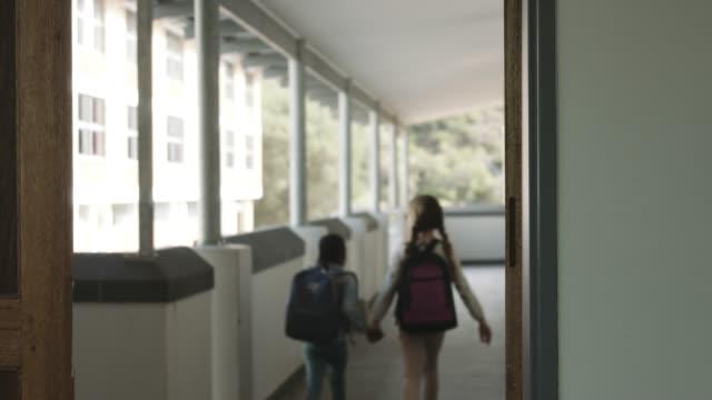 vídeos de stock, filmes e b-roll de girls walking in corridor at elementary school - vista traseira