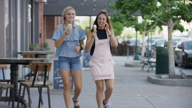 girls walking on city sidewalk eating ice cream cones / provo, utah, united states - brunt hår bildbanksvideor och videomaterial från bakom kulisserna