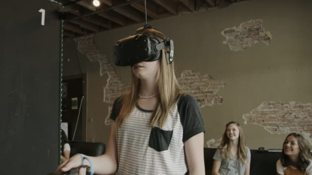 girls watching friend playing virtual reality game at arcade / provo, utah, united states - provo stock videos & royalty-free footage