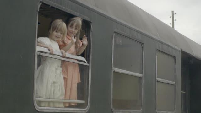 Mädchen aus einer alten Züge Dampfkabine winken