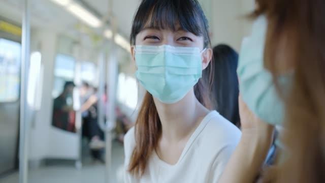 vídeos y material grabado en eventos de stock de chicas que usan máscara facial para protegerse en la plataforma de la estación de metro - accesibilidad