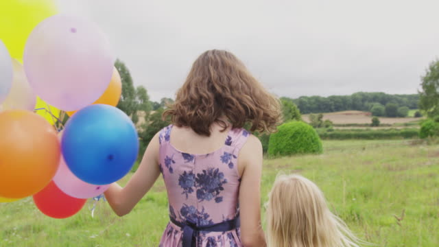 girls with balloons in field - floral pattern stock videos & royalty-free footage