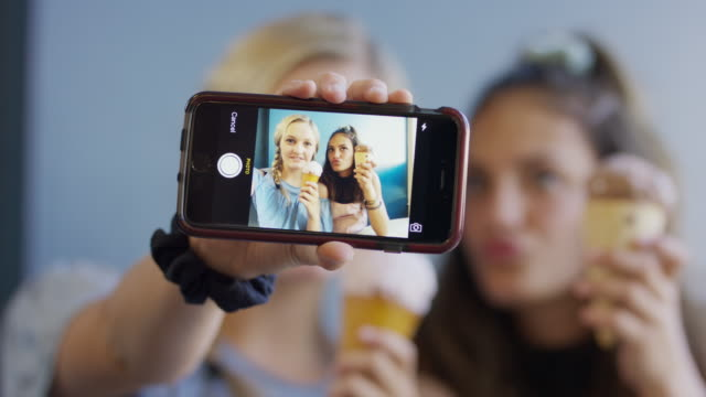 vídeos de stock, filmes e b-roll de girls with ice cream cones posing for cell phone selfie for social media / provo, utah, united states - celular com câmera