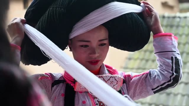 vídeos de stock, filmes e b-roll de girls with large headpieces made from the hair of their ancestors wearing intricately patterned dresses dance in isolated villages in southwest china... - southwest usa