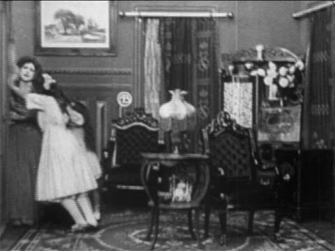 stockvideo's en b-roll-footage met b/w 1909 girls + woman pushing against door frantically in elegant drawing room / film - 1900 1909