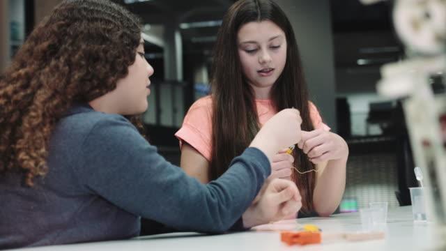 Girls working with chemist set