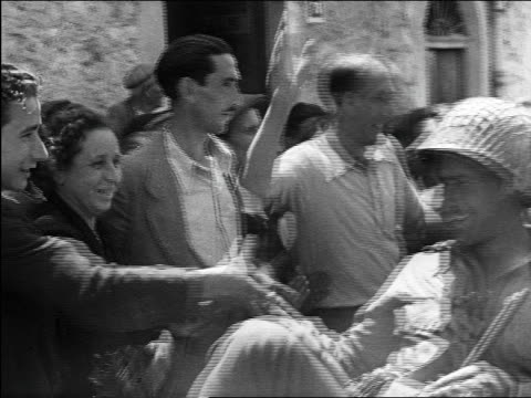 stockvideo's en b-roll-footage met gis in offroad vehicle shaking hands with grateful crowd on village street / sicily / documentary - 1943