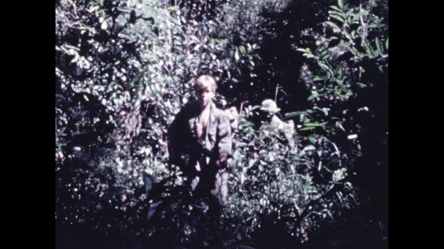 gis pass camera as they move along a narrow path through dense jungle carrying rucksacks and weapons - narrow stock videos & royalty-free footage