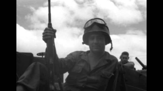 stockvideo's en b-roll-footage met us gis ride in train car of troop train as they move to the battlefront in the korean war / soldier with proppedup rifle looks out window of train as... - slagfront