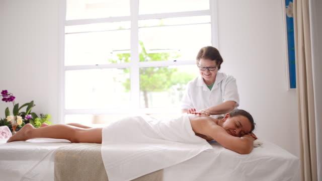 vídeos de stock, filmes e b-roll de fazendo uma massagem nas costas estressante - tratamento em spa