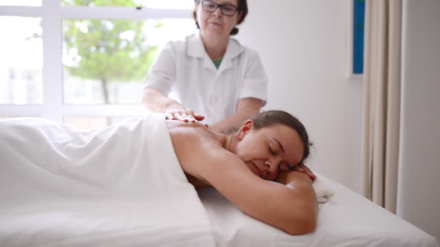 giving a stress-busting back massage - spa treatment stock videos & royalty-free footage