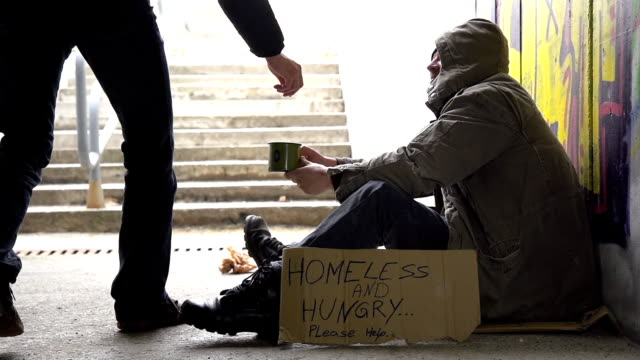 hd super slow-mo: giving coin to a homeless person - giving stock videos & royalty-free footage
