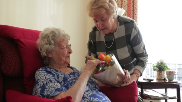 giving flowers to her elderly relative - sheltered housing stock videos & royalty-free footage