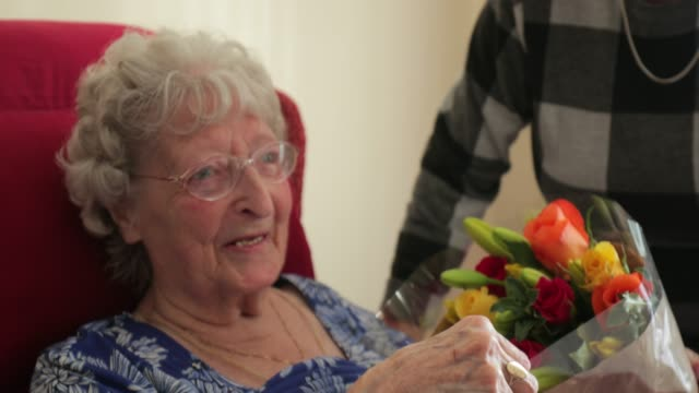 giving flowers to her elderly relative - oggetto creato dall'uomo video stock e b–roll