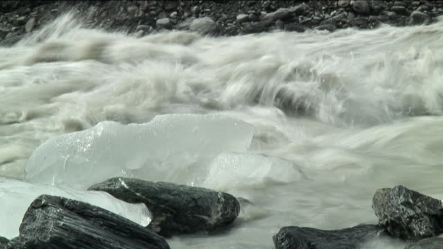 CU Glacial river rushing past rocks and ice chunks / Franz Josef Glacier, New Zealand