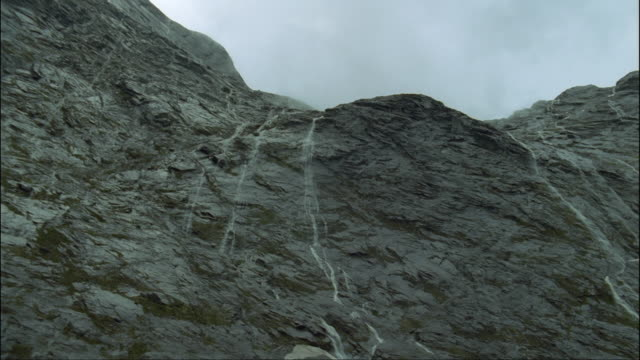 ms, la, pan, glaciated rock face, fiordland national park, south island, new zealand - rock face stock videos and b-roll footage