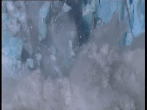 glacier calves into frozen sea - sciogliere video stock e b–roll