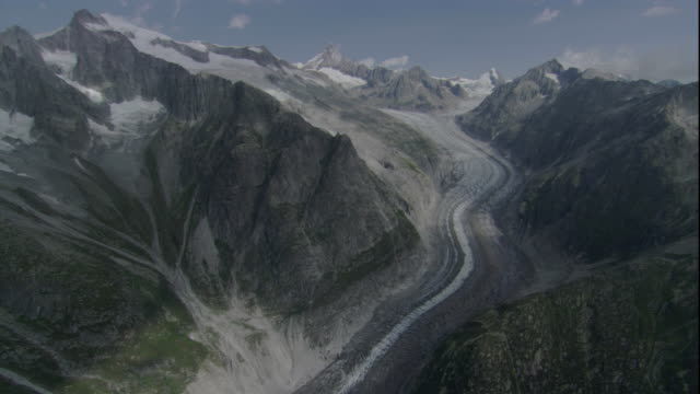 A glacier cuts through a gorge in the Swiss Alps. Available in HD.