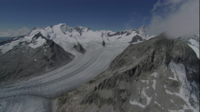 A glacier cuts through the Alps in Switzerland. Available in HD.