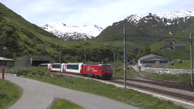 Glacier Express train comes just out of the Furka tunnel at Realp