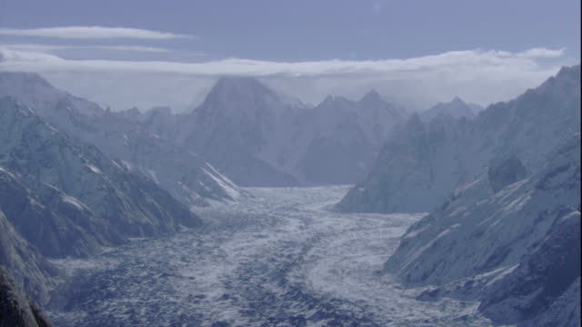 vidéos et rushes de a glacier fills a valley between snow-covered peaks of the karakoram range. available in hd. - pakistan