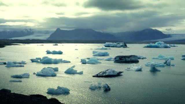 vídeos de stock, filmes e b-roll de lagoa glaciar com céu dramático - reflection