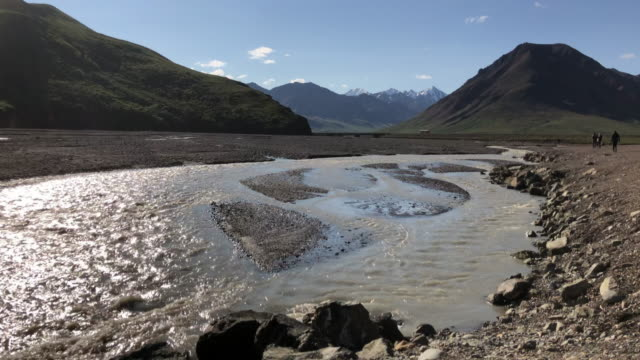 glacier stream and tour bus in distance in the denali national park, alaska - denali national park stock videos & royalty-free footage