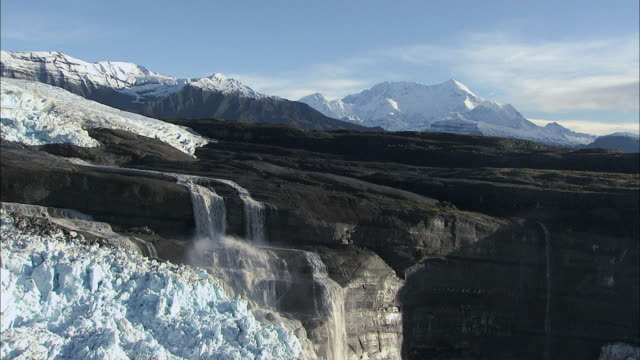 aerial glaciers melting into cascading waterfalls / alaska, united states - falling water stock videos & royalty-free footage