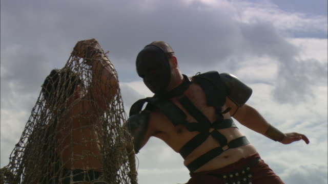 A gladiator uses a trident to kill a man tangled in a net.