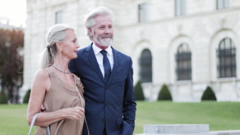 glamorous senior couple walking towards opera on luxury holiday - grey hair stock videos & royalty-free footage