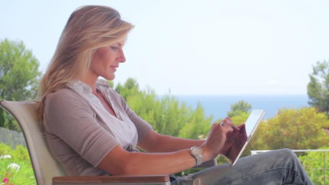 ms glamorous woman using tablet computer, mallorca - 腕時計点の映像素材/bロール