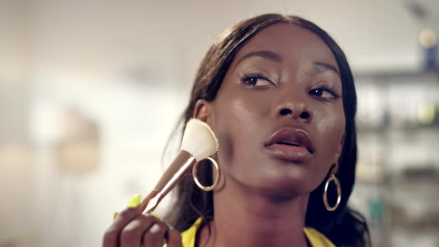 glamour african ethnicity woman putting on makeup - make up brush stock videos and b-roll footage
