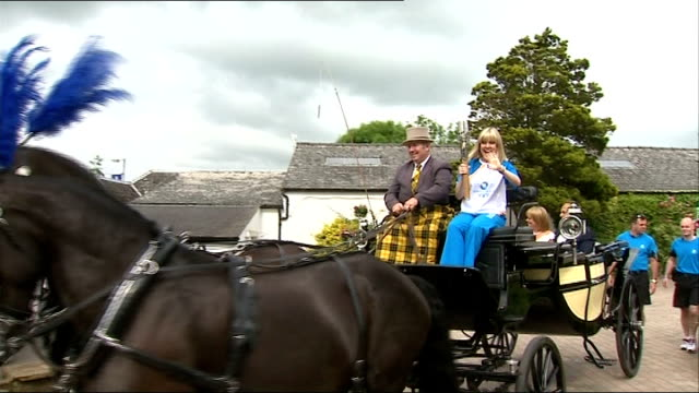 baton passes through gretna green on wedding carriage scotland dumfries and galloway gretna green ext local baton bearer sam pattinson along street... - galloway scotland stock videos & royalty-free footage