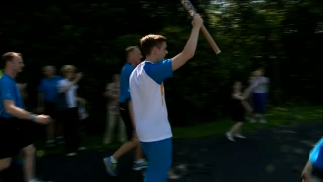 preparations for opening ceremony scotland glasgow ext young man along carrying queens baton man jogging through park as holding baton people taking... - 開会式点の映像素材/bロール