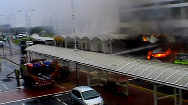 glasgow airport attack: police officers honoured; tx 30.6.2007 fire engine at scene of terror attack, firefighters hosing down burning jeep - the glasgow airport attack stock videos & royalty-free footage