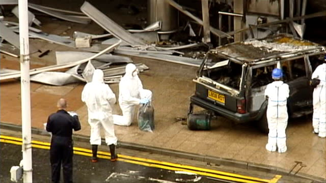 glasgow airport car bomb: aftermath; scotland: glasgow airport: ext high angle shot of police forensic officers removing gas canisters from burnt out... - the glasgow airport attack stock videos & royalty-free footage
