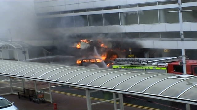 glasgow glasgow airport ext unseen firefighters hose down burning car that has smashed into front of glasgow airport fire alarm and voices of unseen... - glasgow international airport stock videos & royalty-free footage