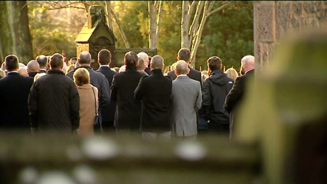 funeral held for three victims from same family church seen beyond trees mourners gathered outside church bv mourners outside church listening to... - itv weekend evening news stock-videos und b-roll-filmmaterial