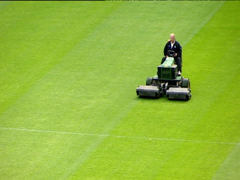 glasgow celtic fc groundsman cutting grass using industrial lawnmower celtic park parkhead glasgow - tosaerba video stock e b–roll