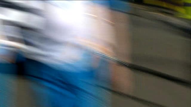 Queen's baton relay Brian Cox at Roslyn Chapel SCOTLAND Midlothian Roslin EXT Police escort along street and relay runners along / baton handover to...