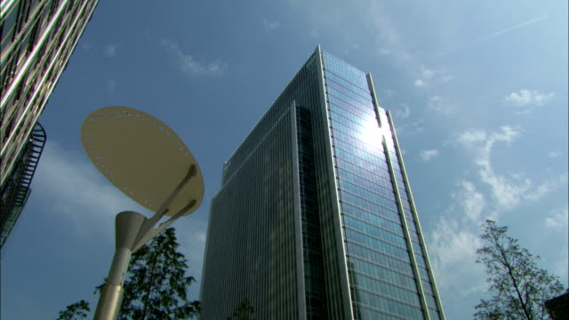 glass and steel skyscrapers reach to a blue sky on london's canary wharf. - blue glass stock videos and b-roll footage