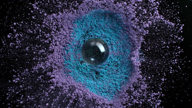 slo mo ld glass ball falling into a pile of blue and violet dust - sphere stock videos & royalty-free footage