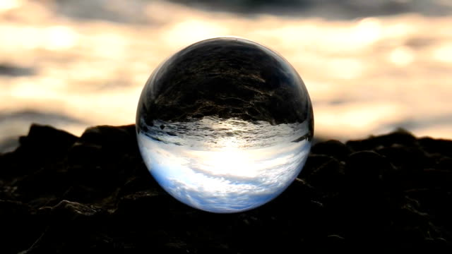 vídeos de stock e filmes b-roll de glass ball on rock in front of sea waves - ball